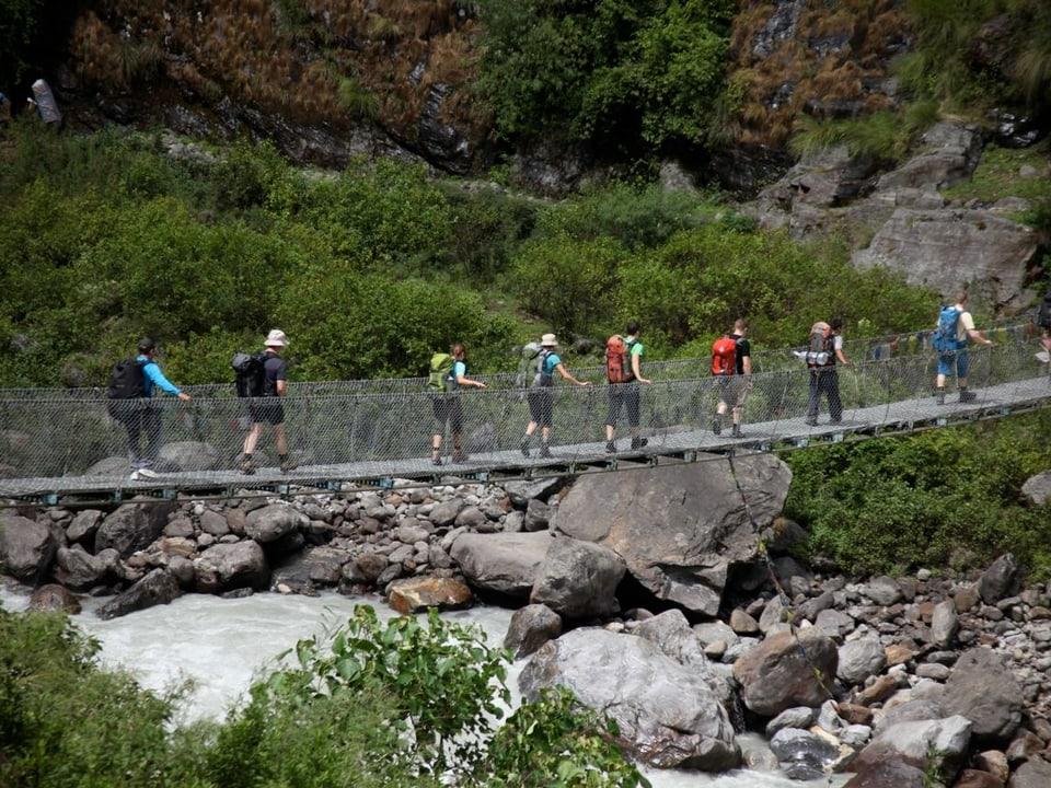 Alpinisten laufen über eine Brücke.