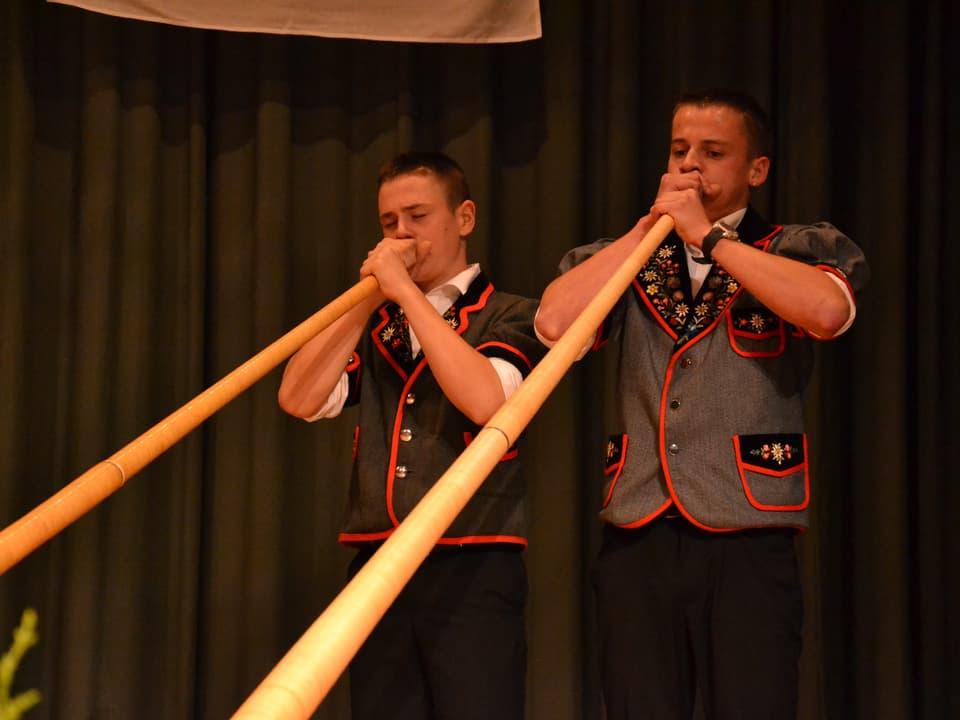 Zwei junge Alphornspieler in Sennenjacken.