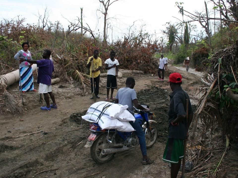 Die Hilfsgüterverteilung ist schwierig. Ein Einwohner versucht, mit seinem Motorrad Lebensmittel in sein Dorf zu bringen.