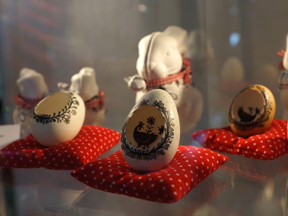 Osterdekoration mit kunstvoll verzierten offenen Eierschalen und Osterhasen.