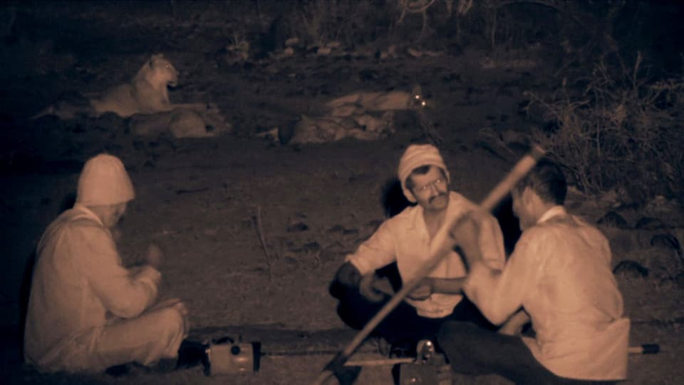 Drei Dorfbewohner sitzen in der Nacht zusammen, im Hintergrund liegen Löwen