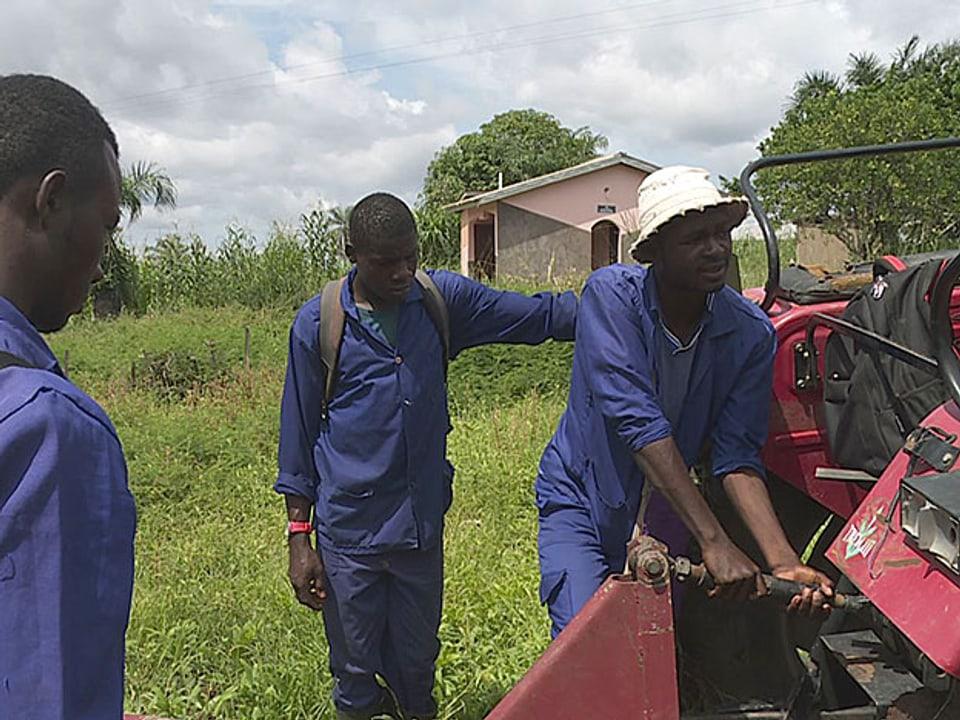 Die Lernenden schrauben am roten Traktor.