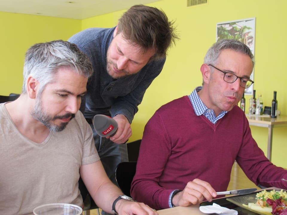 Zwei Männer werden beim Essen von einem Reporter interviewt.