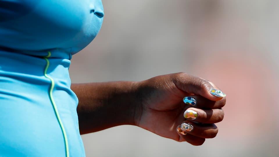 Auf der linken Seite: Serena Williams Oberkörper mit blauem Top. Ihre Hand mit ganz bunten Fingernägeln in allen Farben.