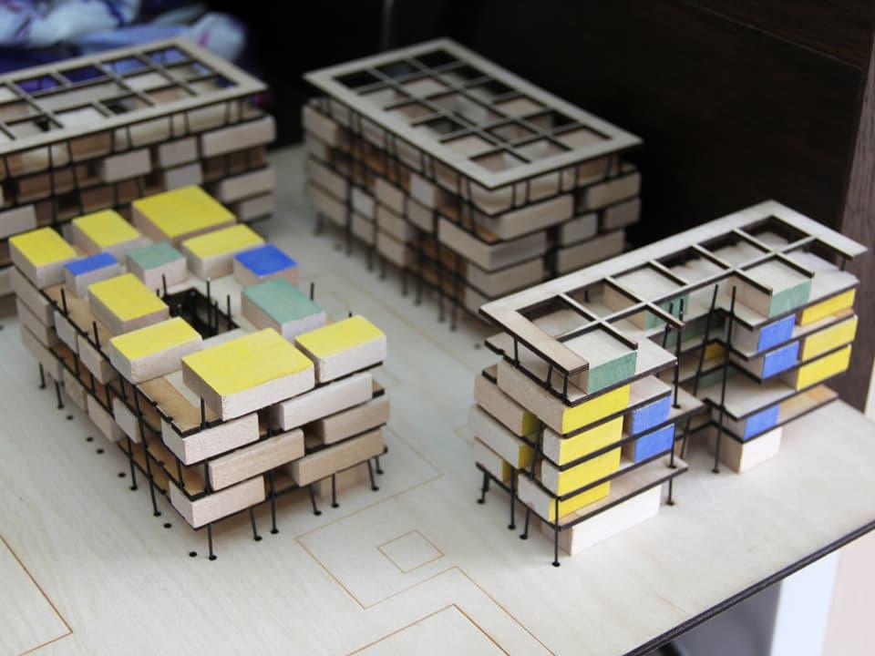 Modell von modernen Stadthäusern mit verschiedenfarbig gekennzeichneten Räumen.
