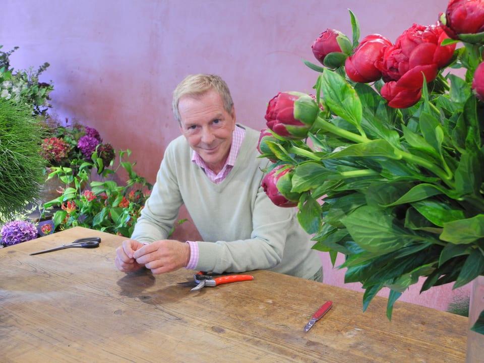 Nach dem Anschneiden der Pfingstrosen stützt sich Kurt Aeschbacher leicht auf dem Holztisch auf. Auf der Arbeitsfläche sind eine Haushaltsschere, eine Gartenschere sowie ein Sackmesser zu sehen. Rechts im Bild zieren die roten Pfingstrosen das Bild.
