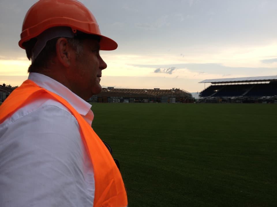 Rolf Gasser, Geschäftsführer vom Eidgenössischen Schwingerverband freut sich auf das Fest. Er ist im Profil mit Schutzweste und Helm zu sehen.