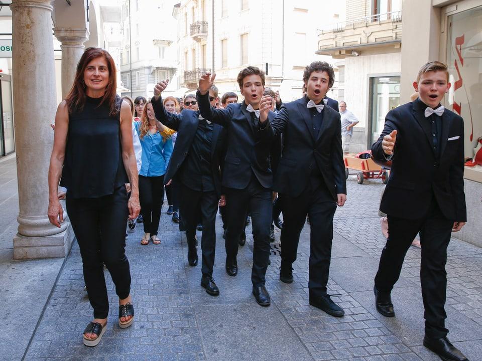 Junge Sänger in dunklen Anzügen singen während sie durch eine Altstadtgasse laufen.