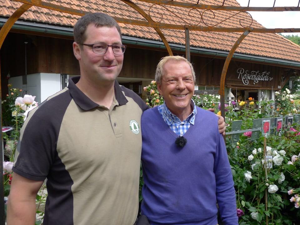 Andreas Reichenbach und Kurt Aeschbacher inmitten der Pergola, umgeben von Rosen.