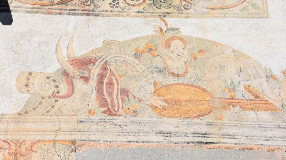 In elefant cotschen ed ina dunna che suna la lauta, maletg sin ina chasa veglia a Scharons.