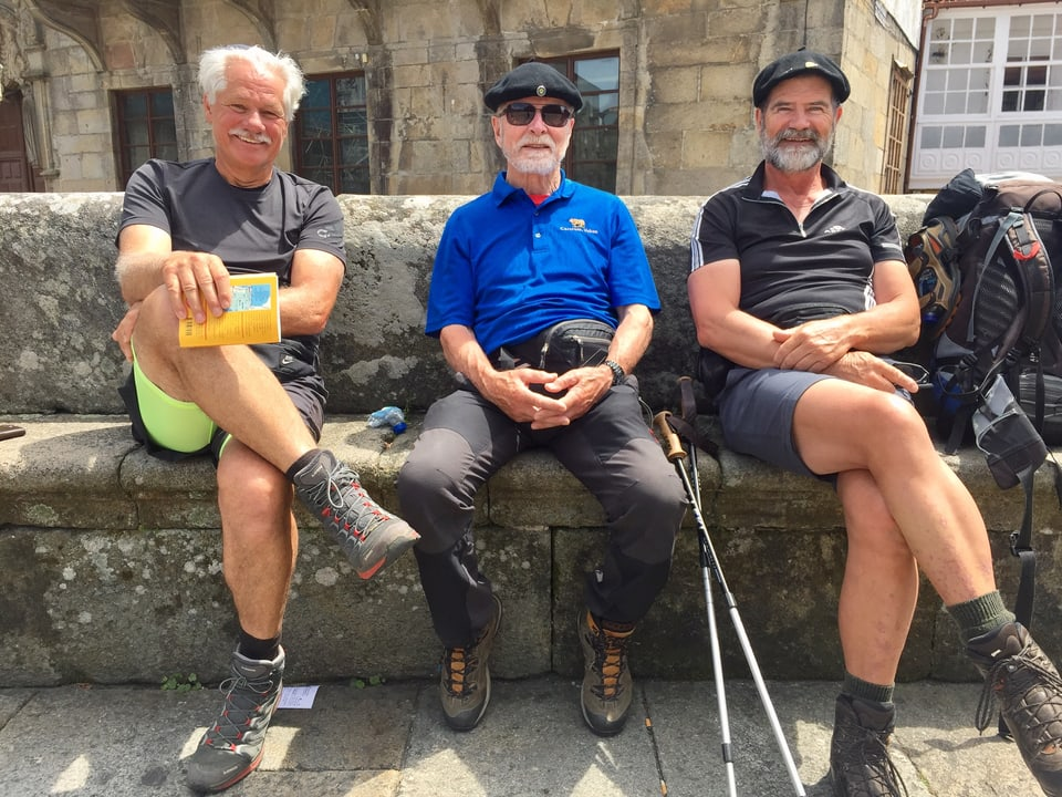 Drei Männer mit Schnauz und Bart ruhen sich auf einer Steinbank aus