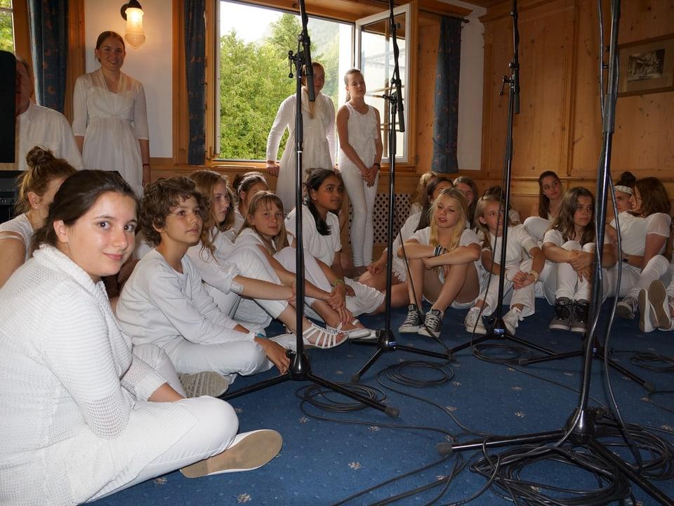 Die Mädchen vom Chor tragen alle weisse Kleidung und sitzen im Halbkreis auf dem Boden.