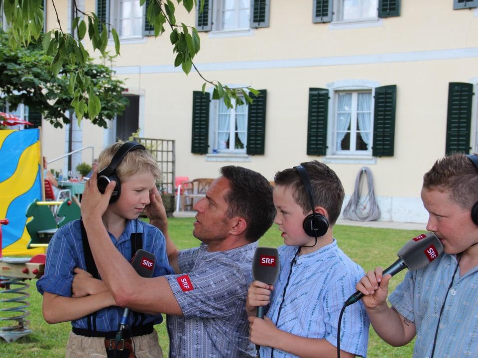 Adrian Küpfer zieht einem Jungschwinger einen Kopfhörer an.