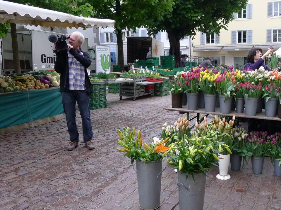 Kameramann Peter Ramseier filmt mit seiner Kamera in die Richtung des Betrachters. Auf dem Pflastersteinboden sind Marktstände zu sehen. Links ein überdachter Gemüsestand, rechts ein Tisch mit mehrheitlich grauen Kübeln mit verschiedenfarbigen Tulpen.