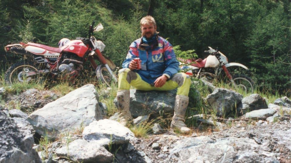 Ruedi sitzt in Motorradmontur auf einem Stein.