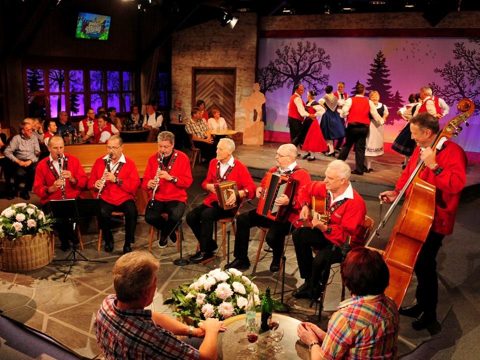 Im Hintergrund tanzen 4 Tanzpaare zur Musik der 7köpfigen Formation Bündner Ländlermix.
