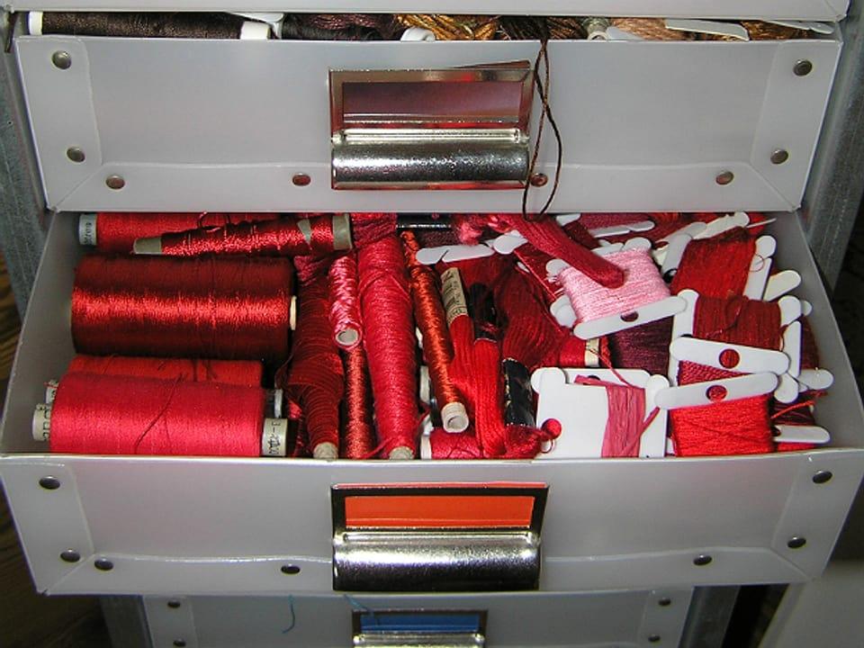 Offene Schublade in Schubladenstock, voll mit Farben in Rottönen