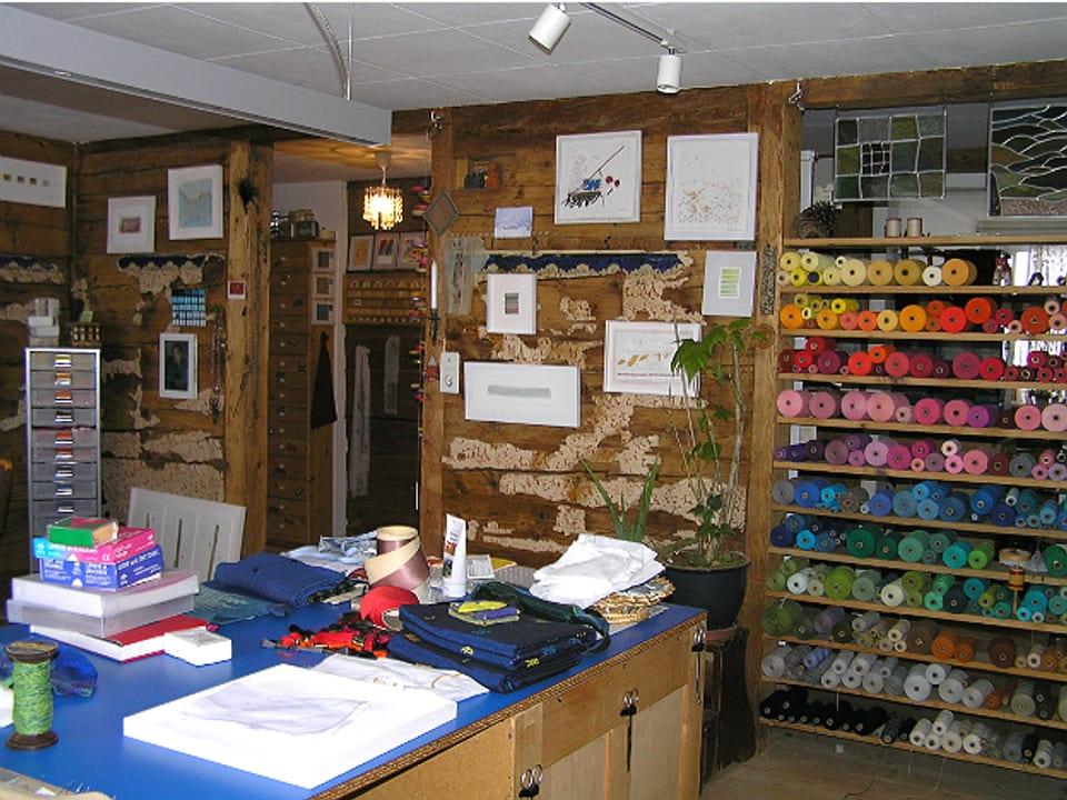 Blick ins Atelier mit Arbeitstisch und Gestell mit Garnen in allen Farben