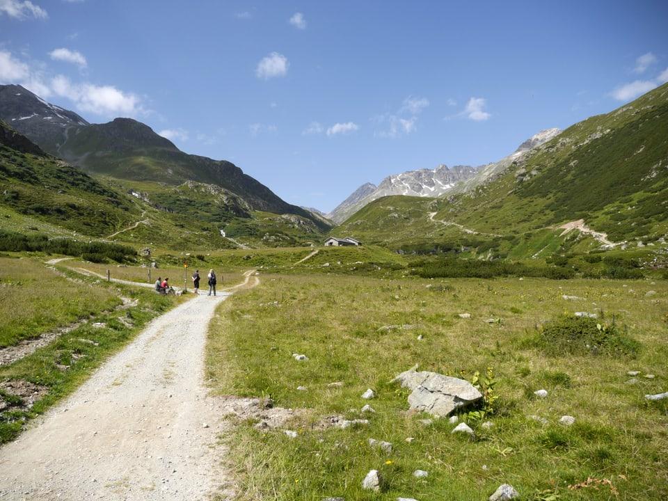 Ein paar Wanderer auf der Alpstrasse, die durch das Val Bever führt.