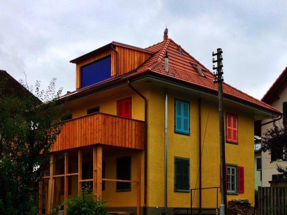 Gelbesd Haus mit unterschiedlich farbigen Fensterläden.