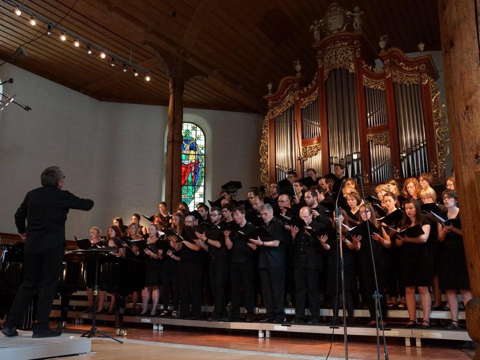 Ein Dirigent vor einem Chor mit Sängerinnen und Sängern in schwarzer Kleidung.