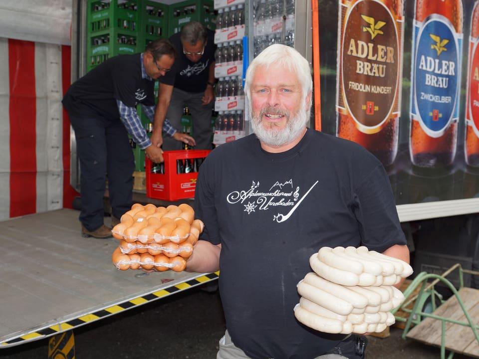 Ein Mann trägt in jeder Hand je ein paar abgepackte Bratwürste.