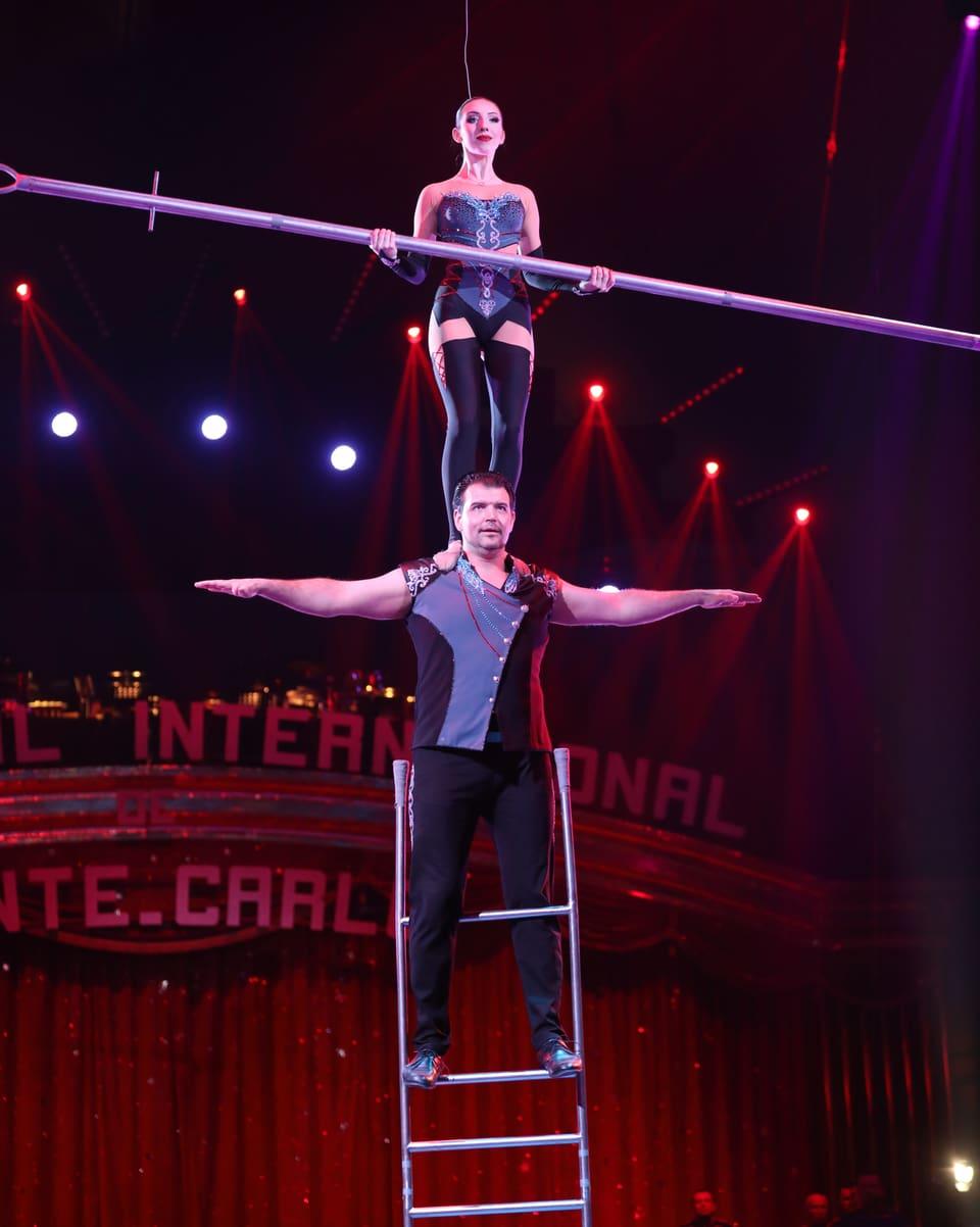 Artist auf der Leiter, Frau steht auf seinem Nacken.