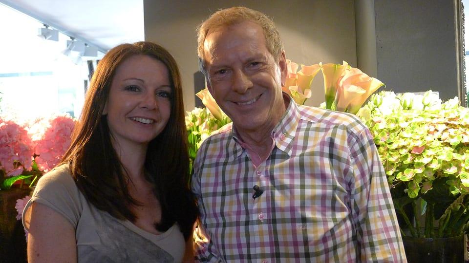 Geschäftsführerin Olivia Hoffmann und Kurt Aeschbacher lächeln vor rosafarbenen und gelbgrünen Hortensien sowie gelben Calla in die Kamera.