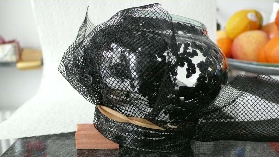 Ein Glas, das auf dem Kopf steht und von einem Netz bedeckt ist.