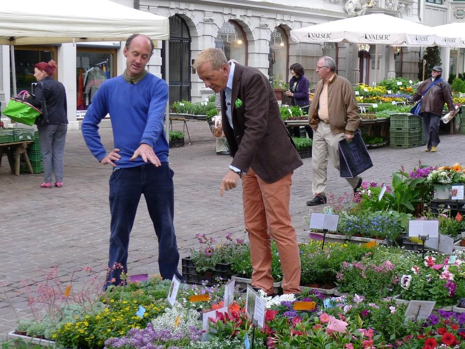 Kurt Aeschbacher steht neben einem Blumenverkäufer und zeigt mit seiner Hand auf Topfpflanzen, die am Boden stehen. Im Hintergrund flanieren Leute durch die Marktstände.