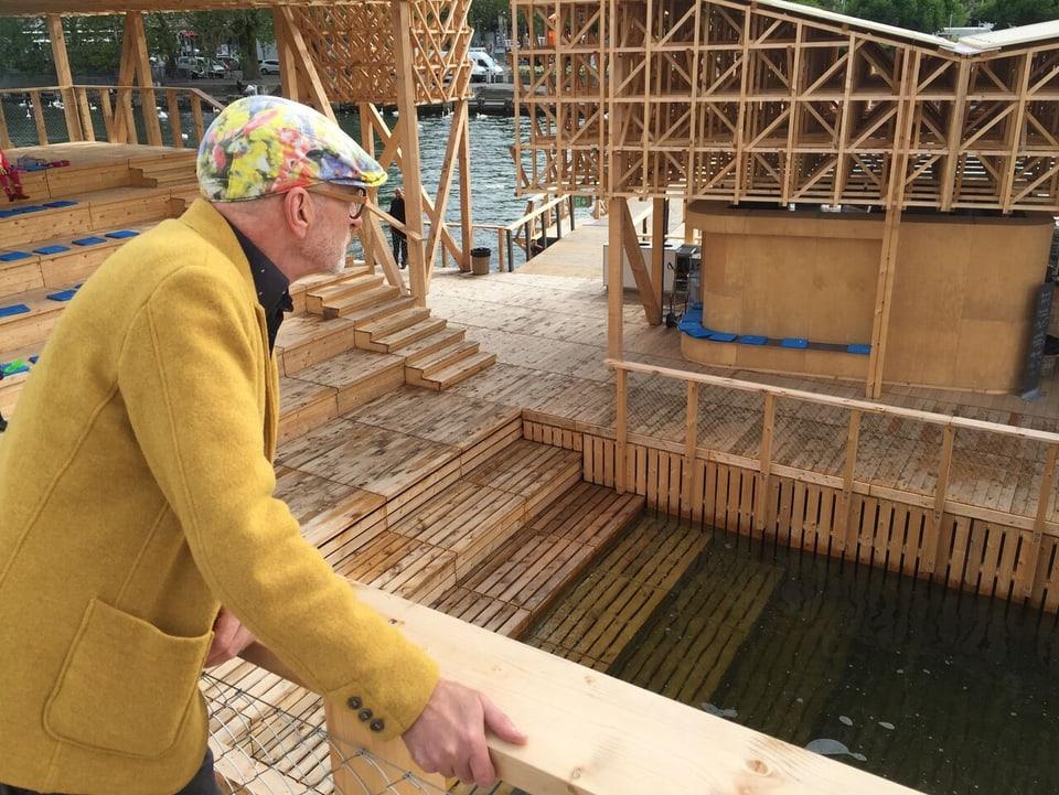Roland Tinguely schaut auf eine Holzkonstruktion.