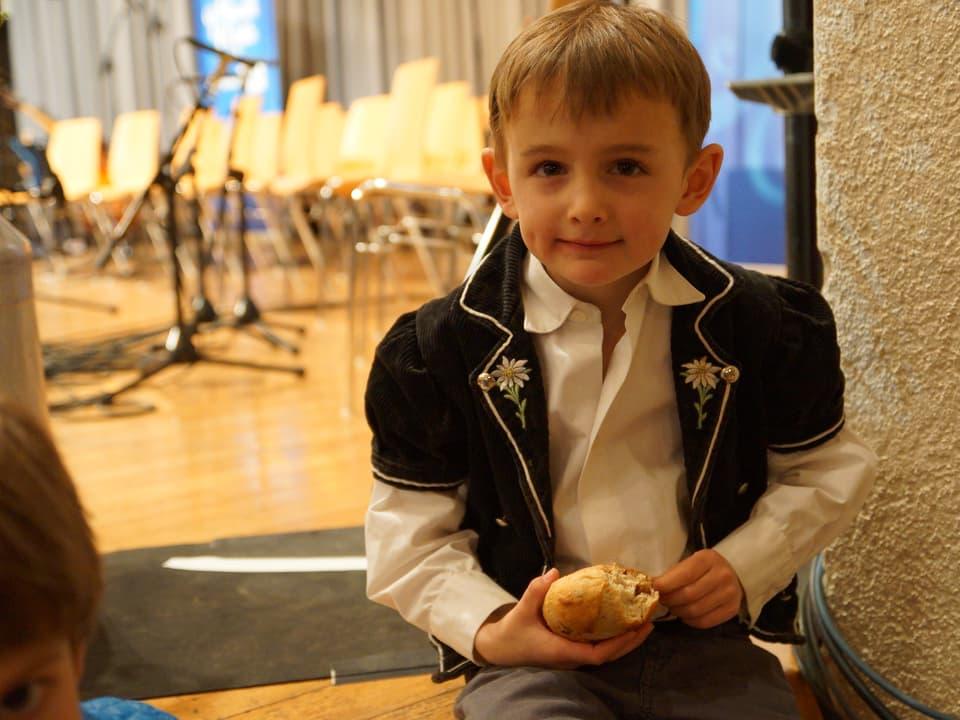 Kleiner Junge mit Semmel in der Hand.