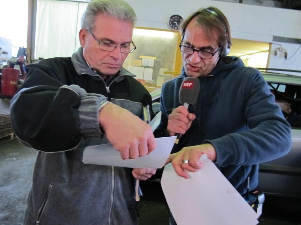 Zwei Männer schauen auf ein Blatt Papier.