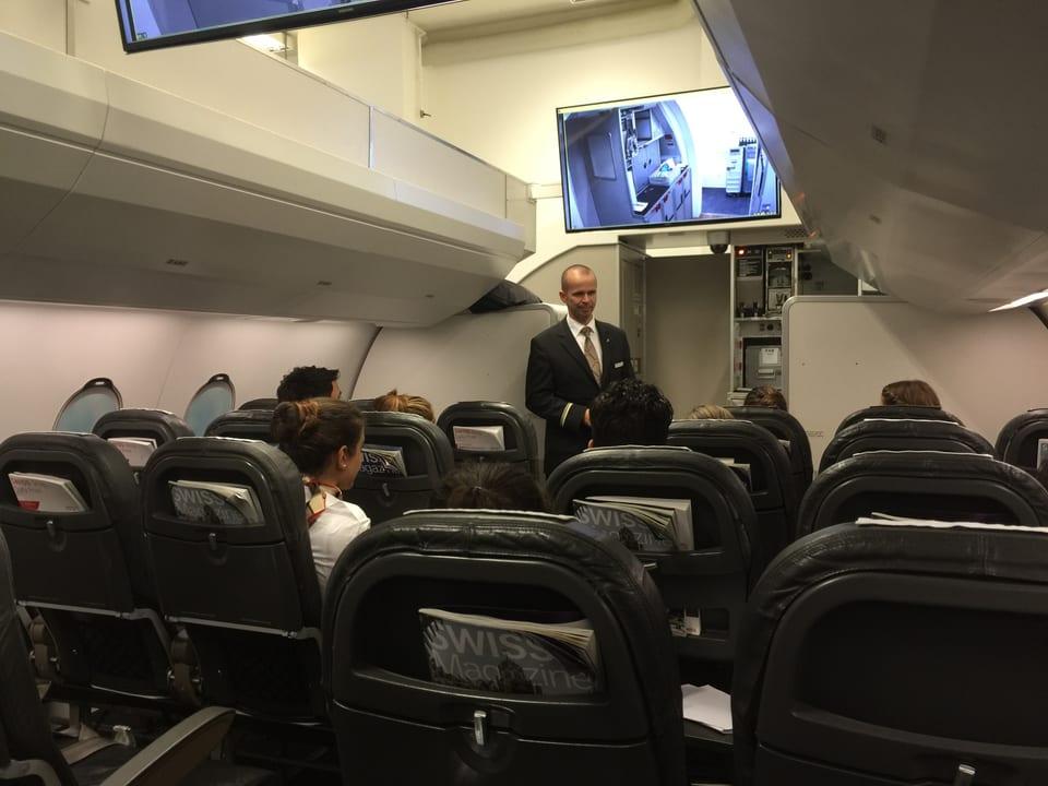 Mann steht in einer Flugzeugkabinen-Attrappe und unterrichtet Flight-Attendants.