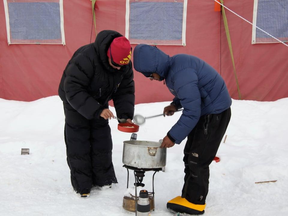 Zwei Sherpas schöpfen sich Suppe aus einem Topf, der auf einem kleinen Gaskocher steht.