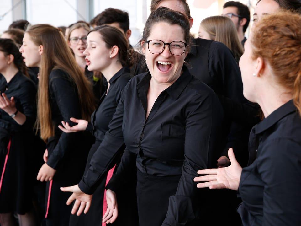 Junge Sängerinnen und Sänger in schwarzen Kleidern mit Rosa Bändern.