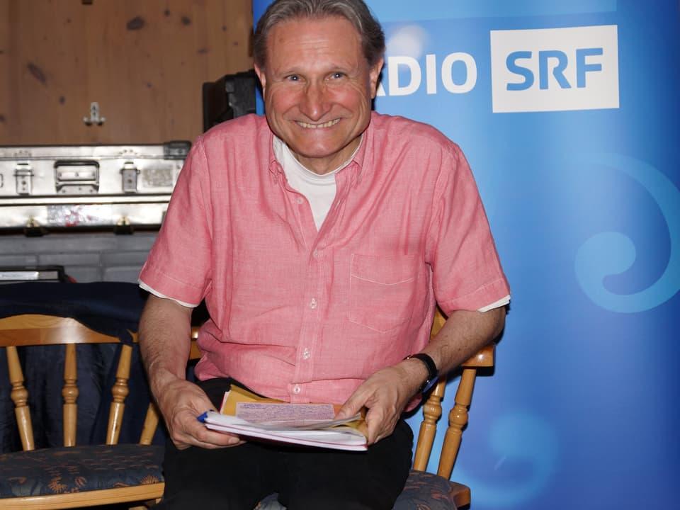 Der Moderator trägt ein rosa Hemd über einem weissen T-Shirt und blickt verschmitzt in die Kamera.