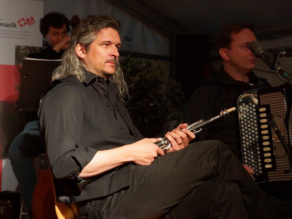 Dani Häusler und zwei weitere Musiker der Kapelle Gupfbuebä auf der Bühne im Festzelt.