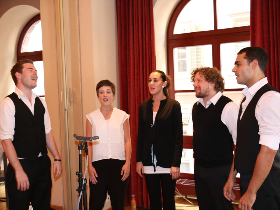 Fünf junge Sängerinnen und Sänger stehen im Halbkreis um Mikrophon herum.