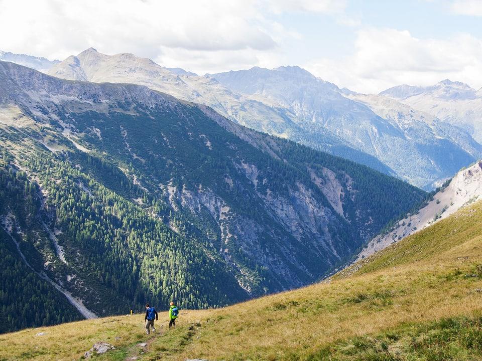 Zwei Wanderer von weitem in der Berglandschaft.