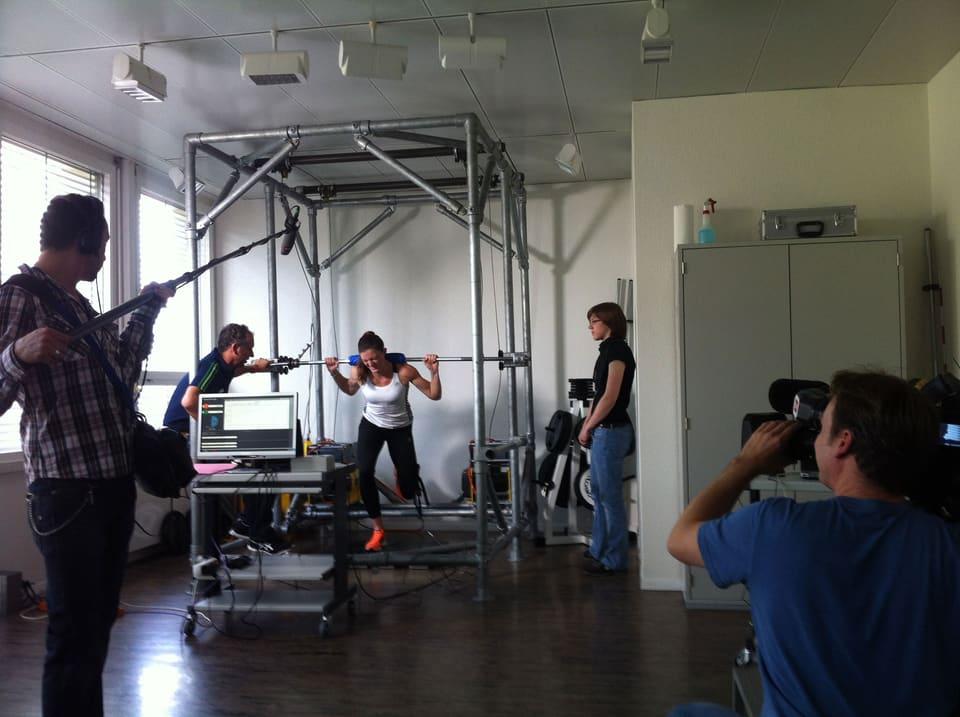 Sportlerin stemmt Gewichte auf einer speziellen Plattform.