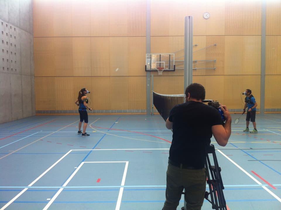 Zwei Sportler werden von einem Kameramann beim Badminton-Spielen gefilmt.