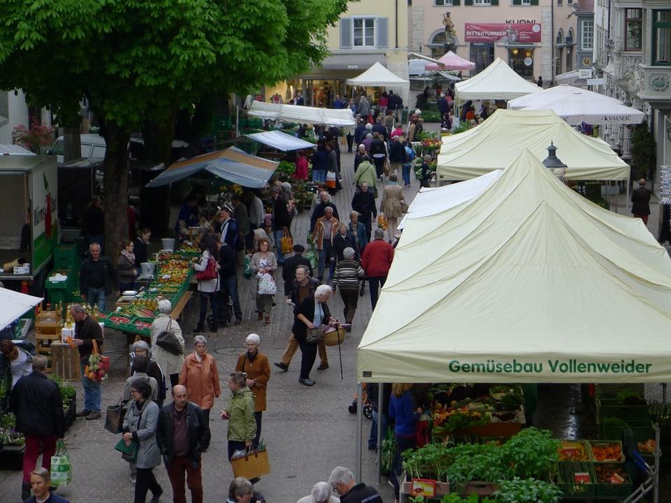 Sicht leicht von oben auf die überdachten Marktstände. Reger Besucherstrom herrscht in der Vordergasse.