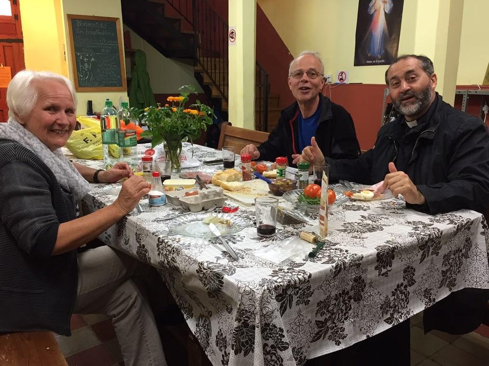 EIn Ehepaar und ein Pfarrer beim Abendessen in einer Pilgerherberge