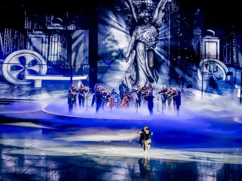 Die Eiskunstläuger Meryl Davis und Charlie White fahren auf dem Eis währen im Hintergrund das Zürcher Kammerorchester spielt.