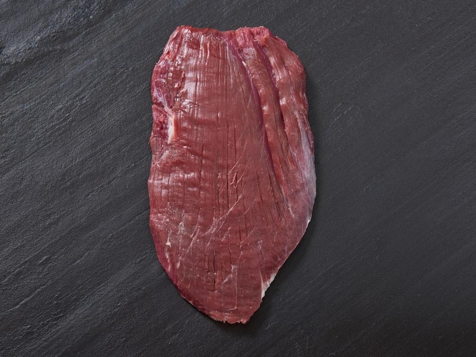 Ein Stück Fleisch auf einer Schiefertafel.