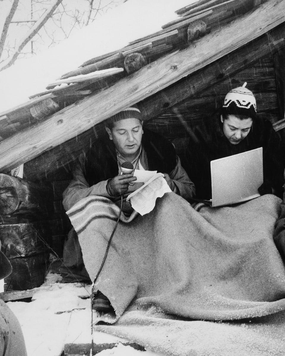Die beiden Reporter sitzen unter einem Dachgiebel, schützen sich mit einer Wolldecke vor der Kälte und berichten live von den Rennen.