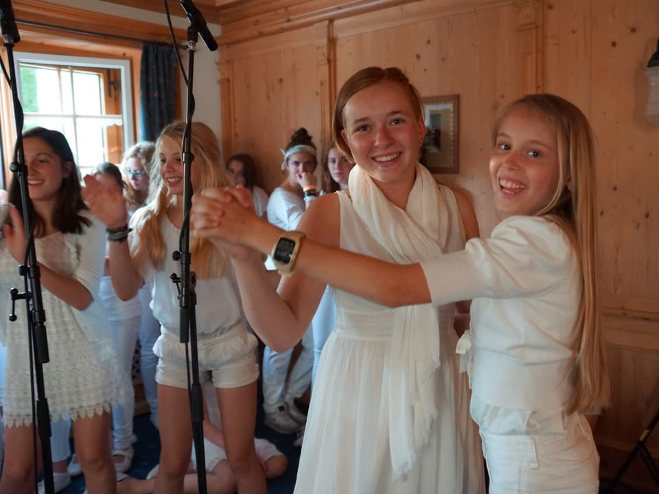 Zwei junge Sängerinnen tanzen während weitere im Hintergrund lachend in die Hände klatschen.