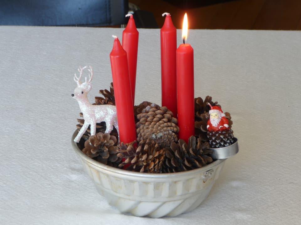 Vier Kerzen in einer Gugelhopfform.