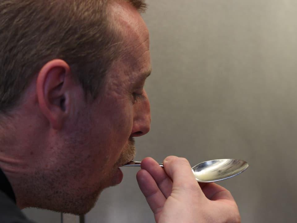 Koch schleckt einen Löffel ab und probiert die Vignagrette.